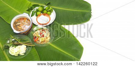 Papaya Slad and Spicy Pork Soup Thai Isan favorite herbal green food for diet control have eat with noodles vegetable lemon cabbageThai morning glory all on banana leaf and right white background or isolate for your word.
