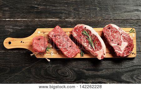 Fresh raw Prime Black Angus beef steaks on wooden board: Tenderloin Denver Cut Striploin Rib Eye