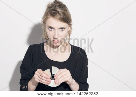 Young blonde woman damaging a compact disc looking to camera over a white background.