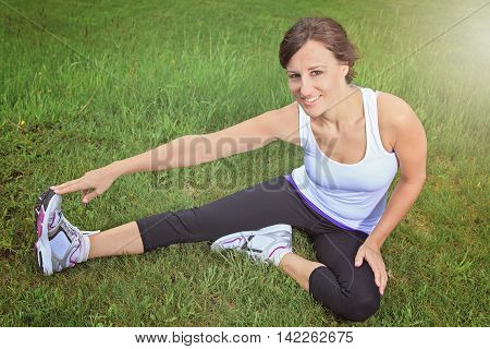 A woman sport in the field and doing some stretching.