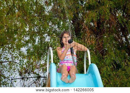 A young girl sits on top of a pool slide with a hose to spray the slide and get it wet.