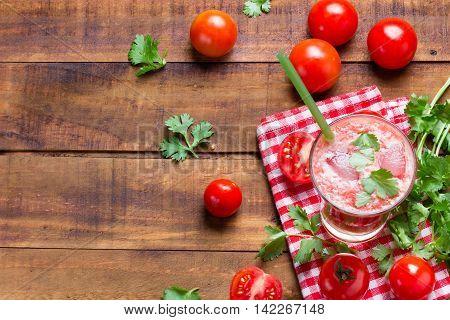 Tomato smoothie juice, fresh tomatoes and cilantro on wooden background
