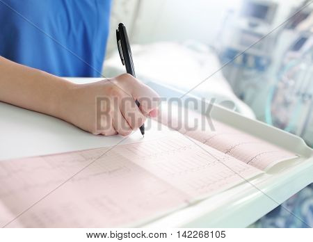 Doctor examines the patient's ECG and writes the description.