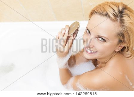 Young Caucasian Blond Female Doing Makeup During Bathing Process.Positive Facial Expression. Skin Treatment. Horizontal Image Orientation