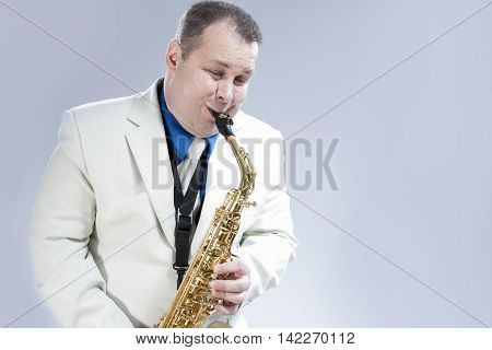 Music Concepts. Natural Portrait of Expressive Male Saxophone Musician Performing in White Suit in Studio. Horizontal Image Orientation