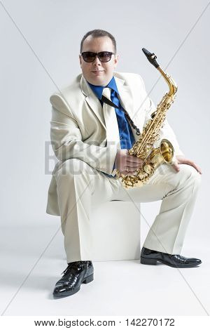 Music Concepts and Ideas. Portrait of Male Stylish Saxophone Player in Sunglasses Posing in White Suit Against White. Vertical Image Composition