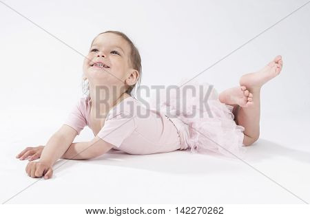 Happy Smiling Caucasian Female Child Laying on Floor Against White Background. Horizontal Image