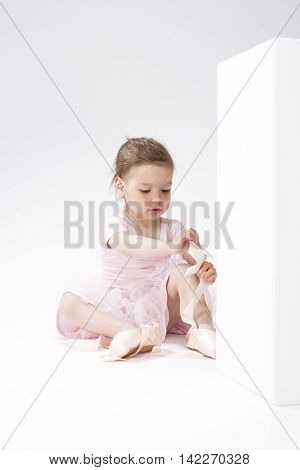 Portrait of Cute Concentrated Caucasian Girl Trying On Miniature Pointes. Sitting on Floor. Against White. Vertical Shot