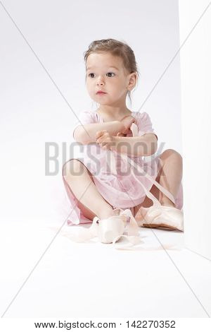 Portrait of Surprised Little Caucasian Ballerina Trying On Miniature Pointes. Posing Against White Background. Vertical Image Orientation