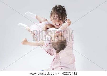 Portrait of Young Caucasian Female and Her Little Daughter Playing and Embracing Together. Against White. Horizontal Image