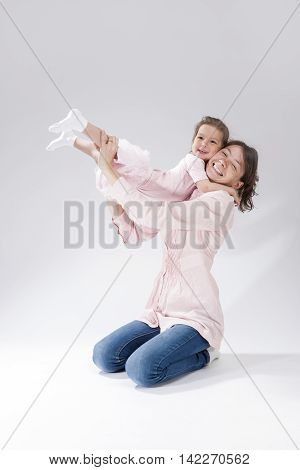 Portrait of Mother and Little Daughter Together Having Fun and Embracing. Posing Against White. Vertical Image