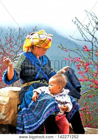 HA GIANG, VIETNAM, February 13, 2016 the mother and children, ethnic Hmong, Ha Giang mountainous region, Vietnam, sitting embroidered brocade, in the spring