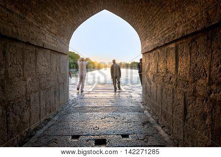 ISFAHAN IRAN - MAY 2 2016 : Iranian people making exersize with sunrise on Kahju Bridge. Khaju Bridge is a bridge in Isfahan Iran. Built by the Persian Safavid king.