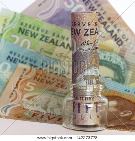 New Zealand dollars in a glass jar.