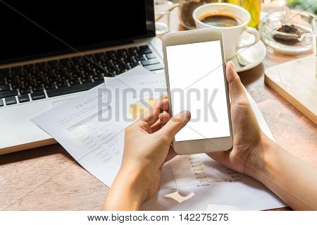 Close up of a woman using smart phone with blank mobile and cup of coffee .Smart phone with blank screen and can be add your texts or others on smart phone.Smart phone concept.