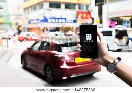 HONGKONGCHINA - MAY 162016 : A man hand holding Uber app showing on LG G4 on road and red carUber is smartphone app-based transportation network.
