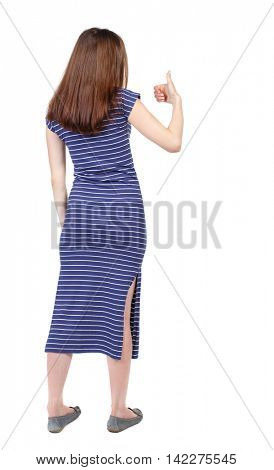 Back view of  woman thumbs up. Rear view people collection. backside view of person. Isolated over white background. The brunette in a blue striped dress shows thumb up.