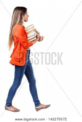 Girl comes with  stack of books. side view. Rear view people collection.  backside view of person.  Isolated over white background. girl in a red jacket goes to the side with a stack of books.