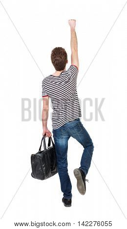 Back view of  man with bag.  Raised his fist up in victory sign.  Rear view people collection.  backside view of person.  Isolated over white background. Curly boy in a striped vest with a bag depicts