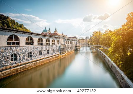 View on Ljubljanica river with building and church in Ljubljana city in Slovenia. Long exposure image technic with reflection on the water