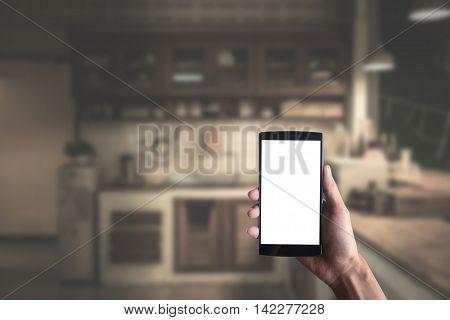 Close up of a man using smart phone with blank mobile and kitchen room blur background .Smart phone with blank screen and can be add your texts or others on smart phone.