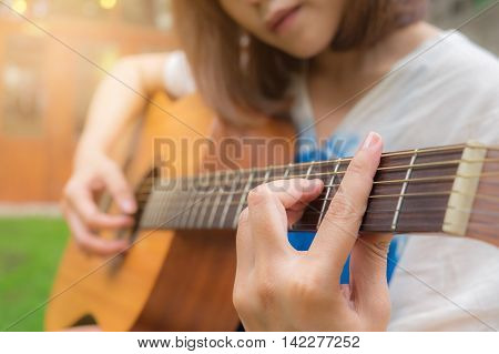Woman's hands playing acoustic guitar close up. Vintage filter effect.