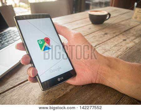 CHIANG MAI THAILAND - MAY 07 2016: Man hand holding LG G4 with Google Maps application o. Google Maps is a service that provides information about geographical regions and sites around the world.