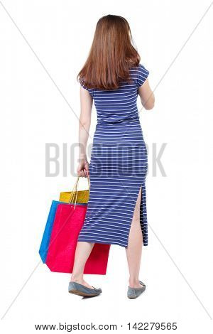 back view of woman with shopping bags. backside view of person.  Rear view people collection. Isolated over white background. The brunette in a blue striped dress standing with shopping bags and