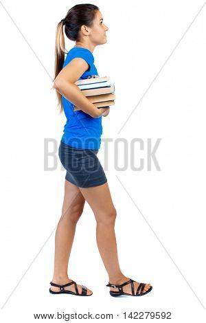 Girl comes with  stack of books. side view. Rear view people collection.  backside view of person.  Isolated over white background. girl in a short skirt and a blue T-shirt goes to the side with books