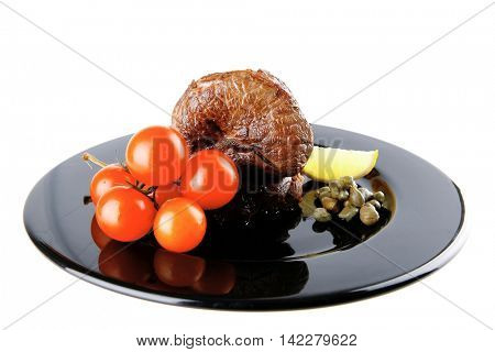 roast meat medallion with cherry tomatoes on black plate