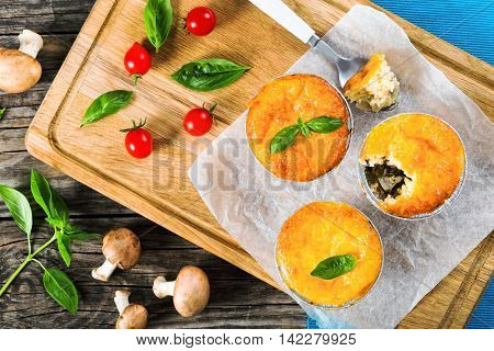 Three portions of French julienne. Mushroom chicken and cheese gratin in Mini Baking cups decorated with basil leaves on paper small bite on spoon top view
