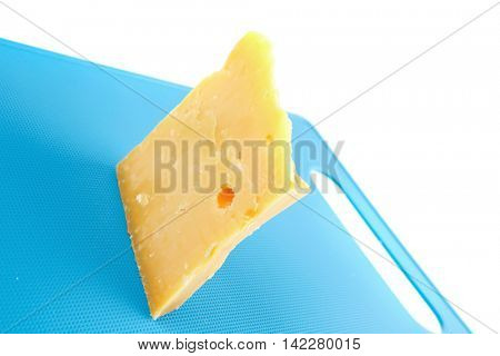 piece of solid edam cheese on blue board