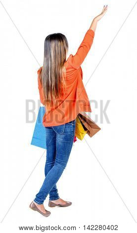 back view of woman  with shopping bags pointing. backside view of person.  Rear view people collection. Isolated over white background. girl in a red jacket standing with paper bags and showing a hand