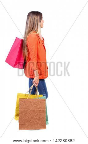 side view of going  woman  with shopping bags . beautiful girl in motion.  backside view of person.  Rear view people collection. Isolated over white background. girl in red coat is throwing his bag