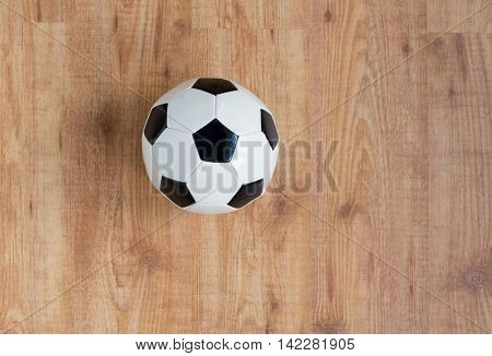 sport, soccer, football and sports equipment concept - close up of ball on wooden floor from top