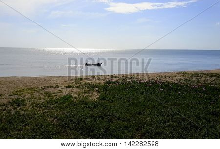 silhouette of man sitting in Thai longtail boat in shimmering sea just off shore, sand in foreground covered in blooming morning glory, camera facing rising sun, Songkhla, Thailand
