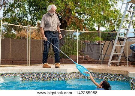 A young girl in a swimming pool places leaves one by one into a skimmer net that her grandfather is holding. He holds it patiently as she helps him. he is wearing slippers out by the pool.