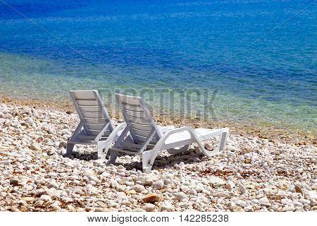 Two deck chairs on beach in sunny autumn day. Mediterranean sea Turkey.