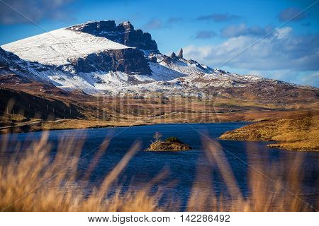 Lock Fada and the snowy Old Man of Storr at spring time with blue sky - Isle of Skye, Scotland, UK