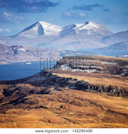 The snowy Scottish Highlands skyline shot from the Old Man of Storr at daytime - Isle of Skye, Scotland, UK