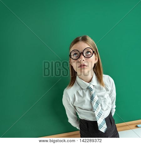 Student standing near the blackboard and looking up. Photo of young student creative concept with Back to school theme
