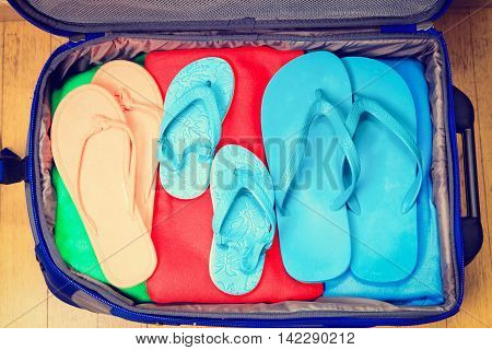 full travel suitcase with clothing and flip-flops, travel packing concept