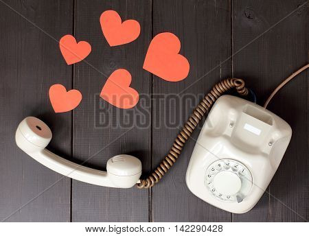 idea attractive voice in the form of hearts flying out of telephone handset lying on a wooden table / amorous talking by phone