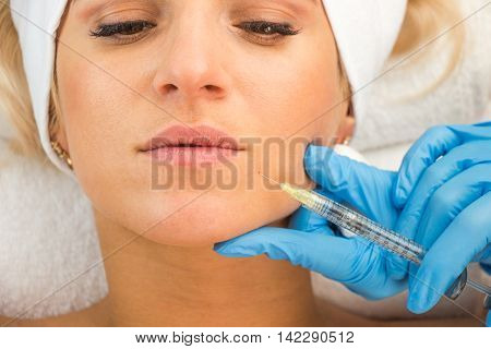 Macro view of young woman face injection hands with medical gloves beauty treatment