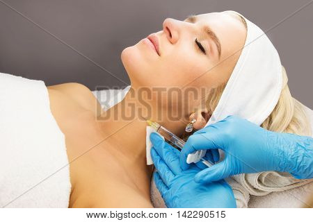 Lying young woman injection hands with medical gloves beauty treatment