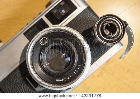 Antique SLR or Reflex camera with film roll over wooden surface