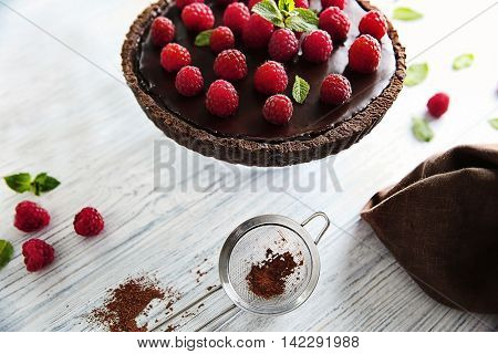 Delicious chocolate tart with raspberry on a wooden background