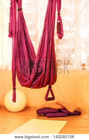 Red hanging hammock indoor with fit ball pillows and mat