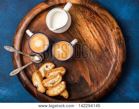 Coffee espresso in cups with cookies and milk in jug on wooden serving round board over dark blue painted plywood background, top view, copy space