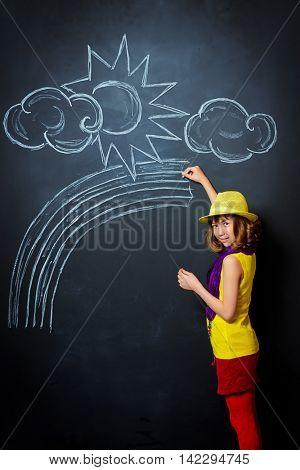 Joyful pretty girl in colorful clothes drawing a rainbow on a blackboard. Happy childhood.